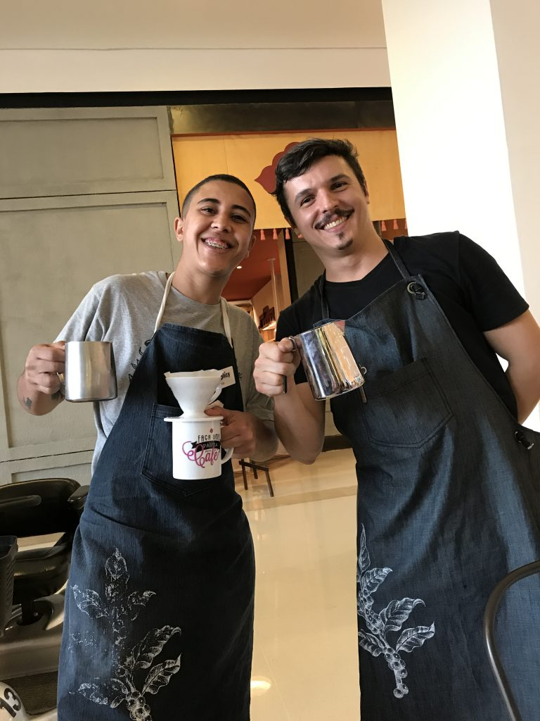 Two young baristas smiling and holding espresso pitchers