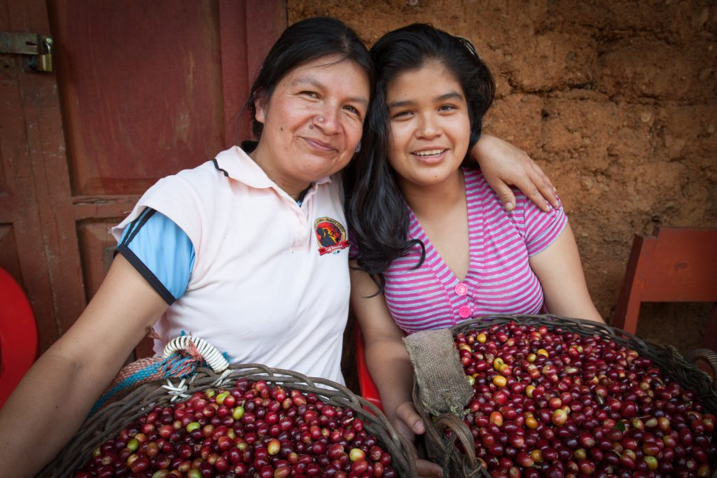Coffee farmer and Cafe Femenino co-founder Erlita Baca Arce with her daughter, Ketty, holding baskets of red hand-picked coffee cherries