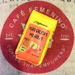 Back of Zingerman's Peru Erlita's Lot coffee on top of the Cafe Femenino logo on a coffee jute bag.